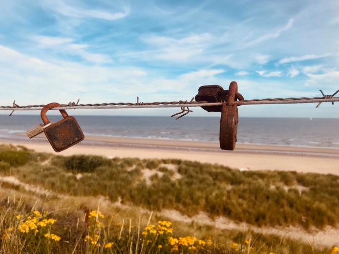 Ook langs het strand in het Belgische De Haan laten verliefde stelletjes hangsloten achter aan het prikkeldraad.