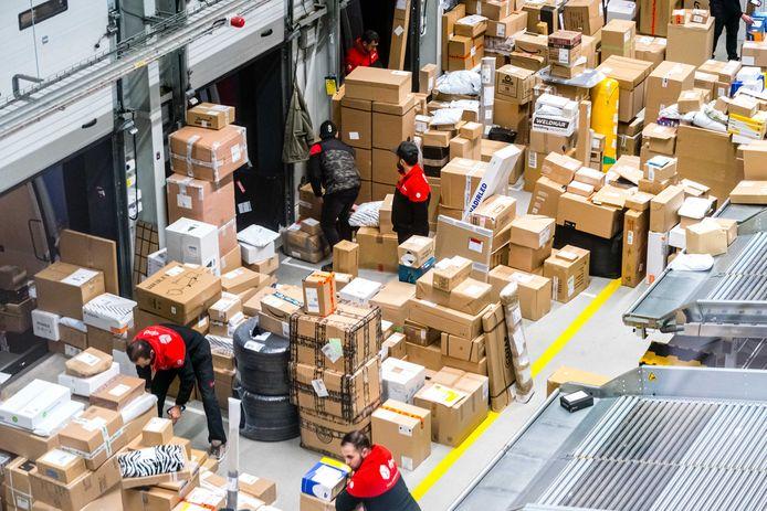 Medewerkers van pakketdienst DPD sorteren pakketjes in het pakkettensorteercentrum.