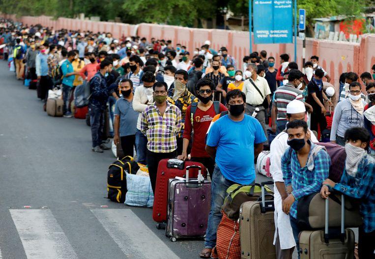 Indiase arbeidsmigranten en hun familie wachten bij het station van Ahmedabad op de trein naar huis. Door de Covid-19-lockdown vielen miljoenen plots zonder werk, wat een massale exodus op gang bracht.