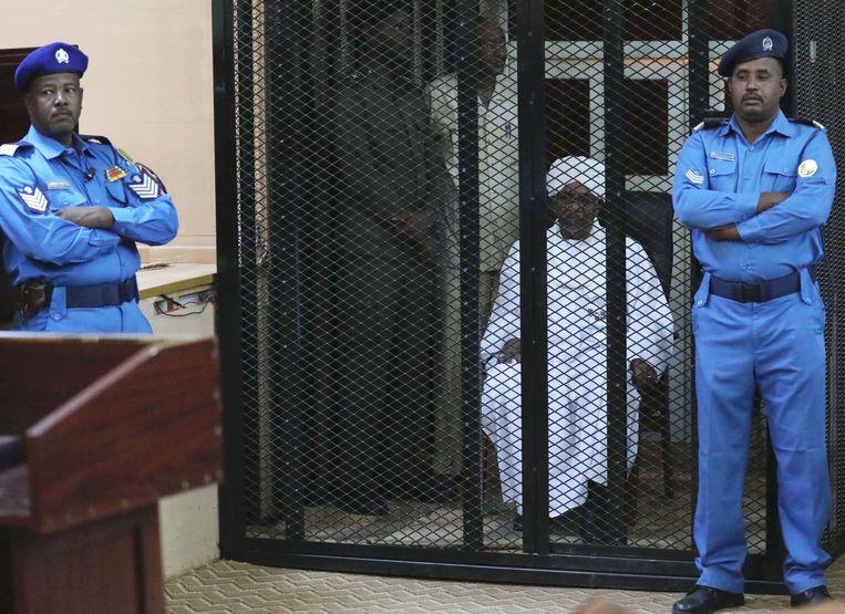 De afgezette dictator Omar al-Bashir hoort in de rechtbank van Khartoem op 14 december vorig jaar het vonnis tegen hem uitspreken wegens corruptie.  Hij kreeg twee jaar gevangenisstraf.  Beeld EPA, Morwan Ali