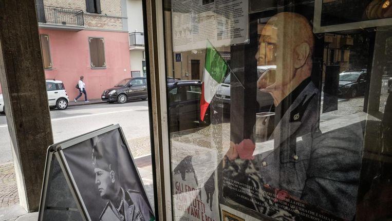 Een van de drie souvenirwinkeltjes in Predappio met Mussolini-posters, Il Duce-sleutelhangers en andere fascistische prullaria. Beeld null