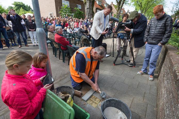 Leo Martens van de gemeente plaatst de stenen in het trottoir voor huisnummer 34, onder toeziend oog van kinderen uit de buurt.
