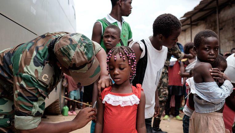 Een meisje in de stad Luanda, Angola, krijgt het vaccin tegen gele koorts toegediend. Beeld epa