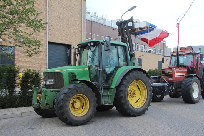 Protesterende tractors toeterend in optocht op de Needseweg nabij het Berkellandse gemeentehuis. De Nederlandse vlag ondersteboven is het symbool van het nationale boerenprotest.