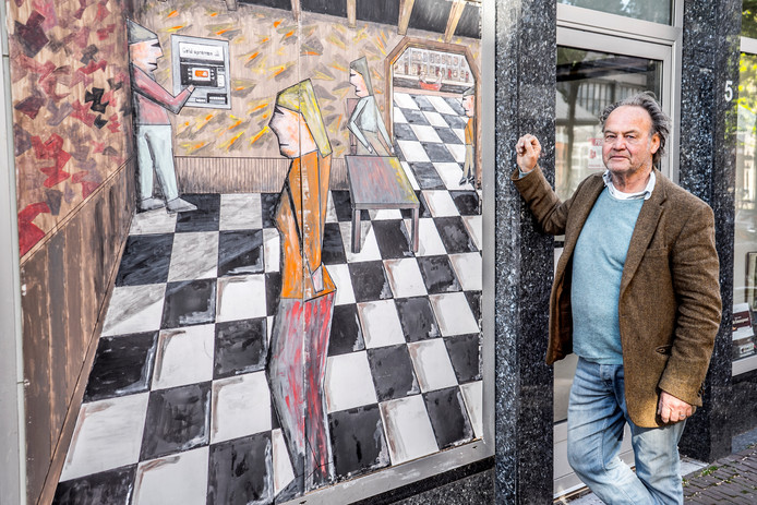 Kunstenaar Tijn Noordenbos bij z'n atelier in de Papenstraat, waar een werk van zijn eigen hand de aandacht trekt.