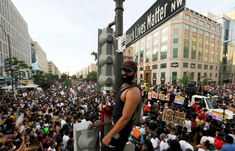 Grote groepen mensen verzamelden zich zaterdag rond het straatbord bij het tot 'Black Lives Matter Plaza' gedoopte gebied nabij het Witte Huis in Washington.  Beeld REUTERS