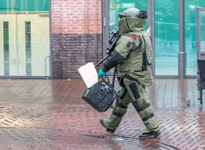 Een medewerker van de Explosieven Opruimingsdienst in beschermende kleding op weg naar Bruut.