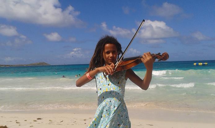 """Tefari op het strand van Sint-Maarten. Haar viool heeft ze meegenomen naar Nuenen. ,,Als ik bang ben, speel ik viool. Dan voel ik me beter."""""""