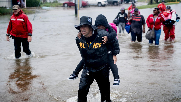 Een agent draagt een kind op de rug in Houston.
