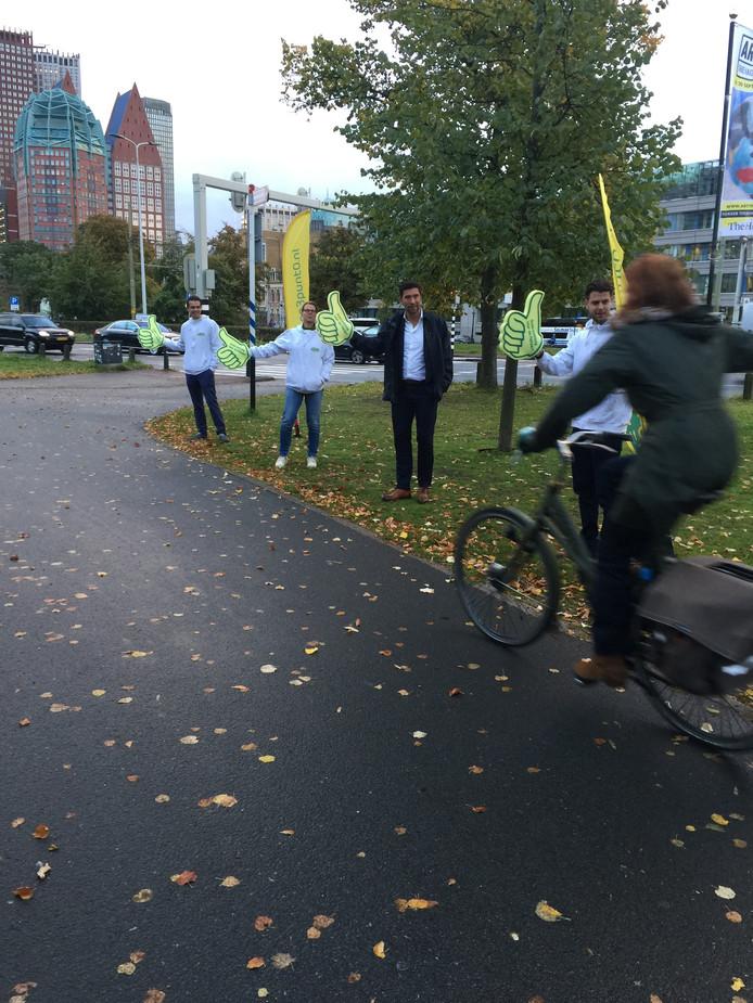 Wethouder Robert van Asten geeft een duim aan fietsers.