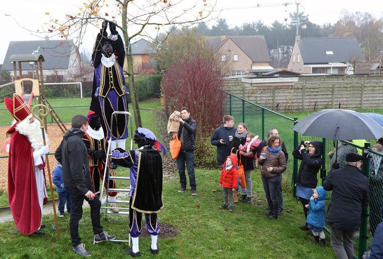 De zwarte pieten hangen de tutters in de boom. Sinterklaas kijkt toe dat zij het goed doen.