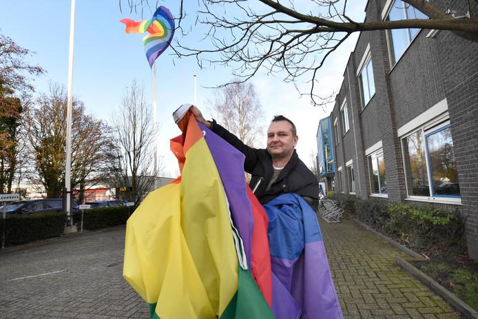 Bode Alex staat op het punt de regenboogvlag bij het gemeentehuis van Woerden te hijsen. Nu wappert nog een 'vredesvlag' met een extra lichtblauwe baan fier aan de mast.