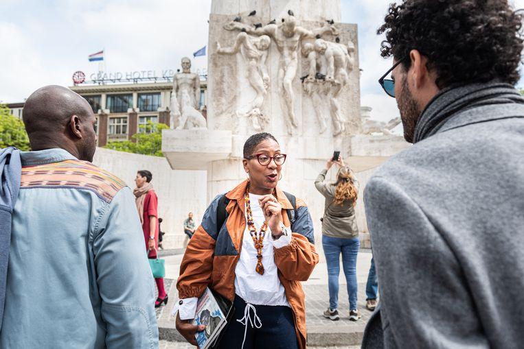Gids Jennifer Tosch tijdens de wandeltour door het centrum van Amsterdam met bijzondere aandacht voor monumenten en gebouwen die een link hebben met slavernij of zwarte geschiedenis. Beeld Simon Lenskens