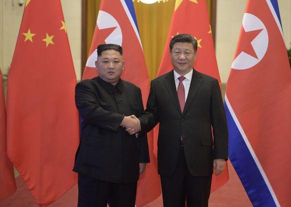 De Chinese president Xi Jinping (rechts) en de Noord-Koreaanse leider Kim Jong-un schudden elkaar de hand.