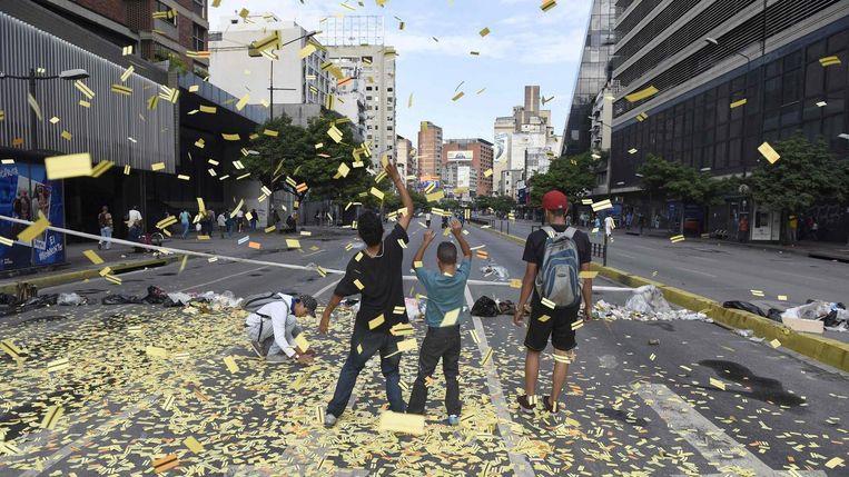Demonstranten strooien ongebruikte metrokaartjes uit over de weg en blokkeren de toegang in Caracas. Beeld afp