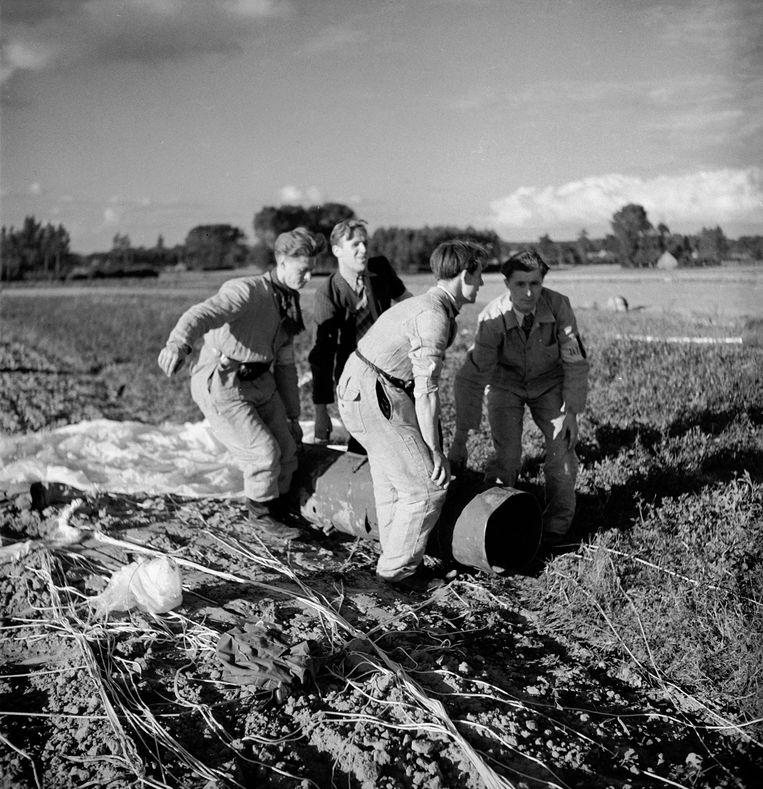 September 1944. Belgische verzetsmensen van De Witte Brigade ontfermen zich over een door de geallieerden gedropt vat vol wapens en ammunitie. Beeld Getty Images