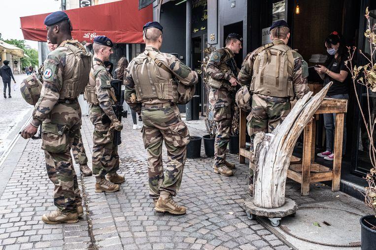 Een groep soldaten bestelt wat te eten en drinken in een restaurant in Parijs op de dag dat Frankrijk haar strikte lockdown-regels verzacht.  Beeld Joris Van Gennip