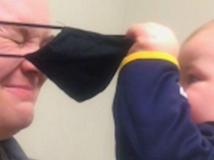 Verveelde baby amuseert zich met mondmasker van mama