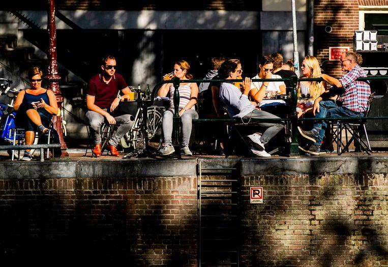 Mensen genieten van zomers weer in Amsterdam. Beeld Hollandse Hoogte /  ANP