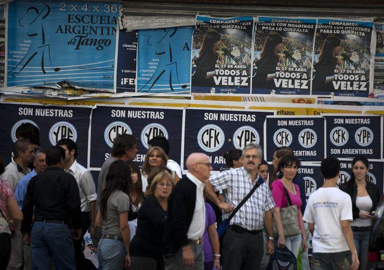 Mensen bij een rij aanplakbiljetten waarop staat: 'Ze zijn van ons. CFK (initialen van de president - red) en YFP. Ze zijn Argentijns'. Beeld ap