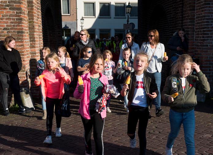 Kinderen van de avondvierdaagse in Montfoort eten al lopend een ijsje.