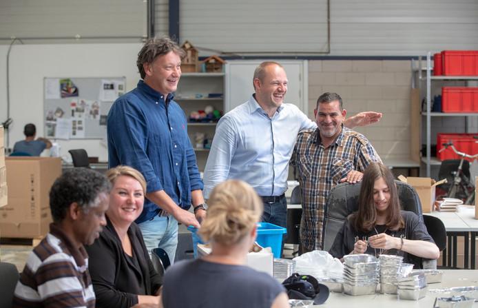 Wethouder Dennis Gudden (derde van rechts), directeur Werkpunt Marc Visschers (staand links) en Ariëla van Ingen, klantmanager gemeente Wageningen (tweede van links) aan het werk met enkele medewerkers van Werkpunt Wageningen.