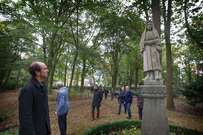 Gedeputeerde Henri Swinkels (l) bekijkt het beeld van de H. Bernadette in het Processiepark in Mariahout, vergezeld door de wethouders Briels en Meulensteen en vertegenwoordigers van het waterschap, Zorg om het Dorp en het parochiebestuur.