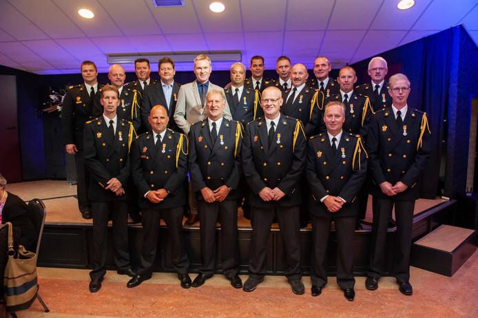De brandweermannen met hun koninklijke onderscheidingen uitgereikt door burgemeester Rehwinkel