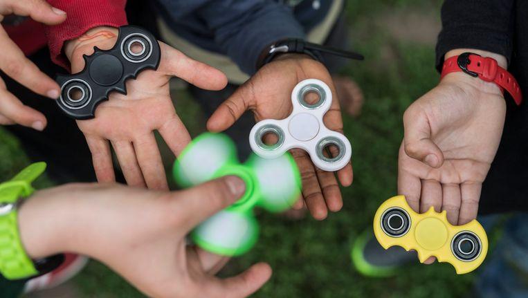 Enkele jongeren spelen met hun fidget spinners. Het speelgoed zou nu echter gevaarlijker zijn dan voordien werd gedacht.
