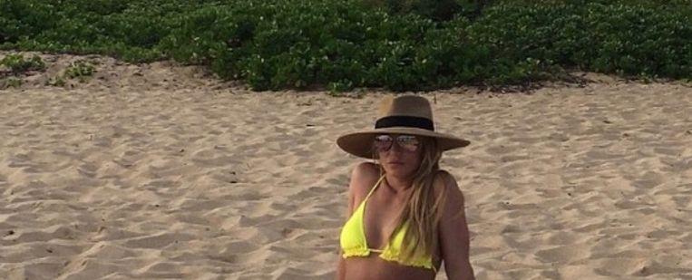 Britney in gele bikini op het strand.