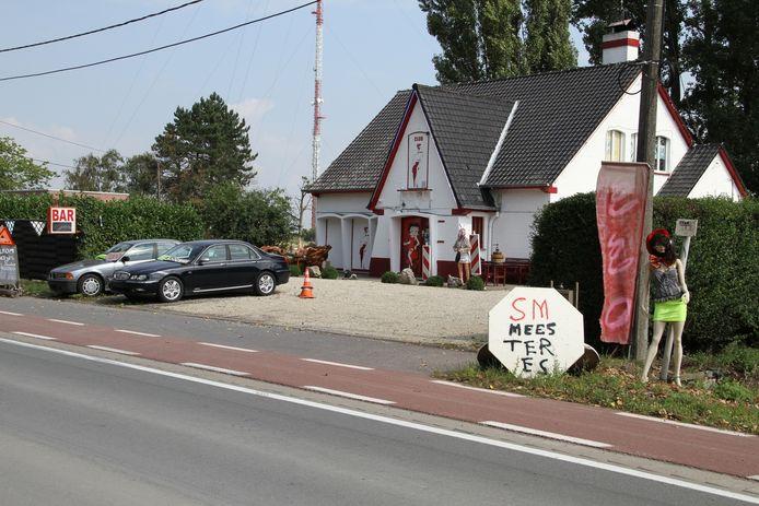 Aan Club Elckerlyc op de Brugsesteenweg nodigt een 'sm-meesteres' de klanten uit om eens binnen te wippen.