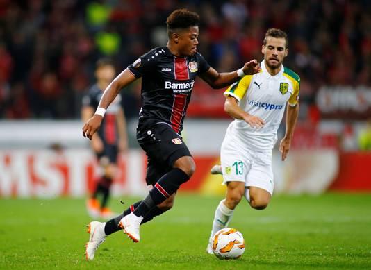 Voormalig ADO-speler Hector Hevel (r) namens AEK Larnaca in actie tegen Leon Bailey van Bayer Leverkusen.