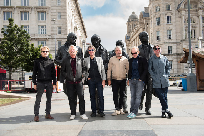 The Analogues poseren bij de beeldengroep van The Beatles aan de Mersey-rivier in Liverpool.