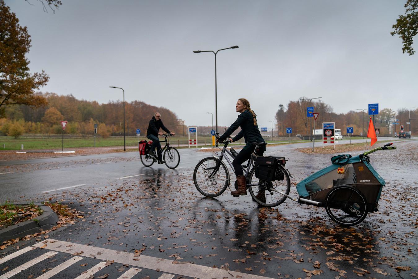 Hiske Feenstra (rechts, met achter zich haar zoon Kris, steekt bij Ellecom de Zutphensestraatweg over om bij de verderop gelegen fietstunnel te kunnen komen. Links Freek te Brinke.
