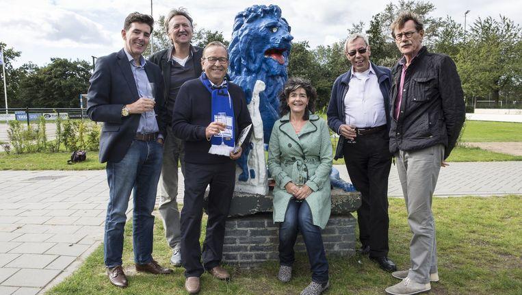 De voorzitter van FC Velsenoord (met sjaal), presentatrice Dieuwertje Blok en leden van het Genootschap bij hun blauwe vondst in Velsen Beeld Willem Sluyterman van Loo