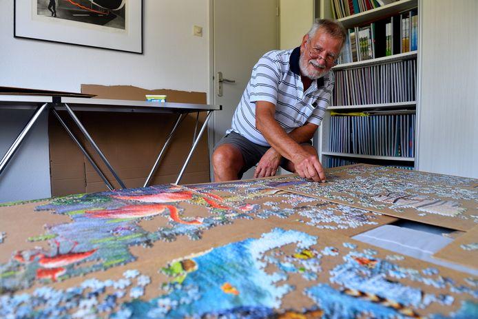 Jan Jonkvorst legt zijn puzzel uit op veertig verschillende stukken karton of hardboard. Achter hem staan plakboeken van vakanties én van puzzelprojecten.