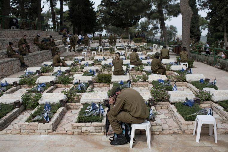 Israëlische soldaten herdenken omgekomen militairen op een begraafplaats in Jeruzalem. Gisteren was in Israël een herdenkingsdag voor door terreur omgekomen militairen. Beeld EPA