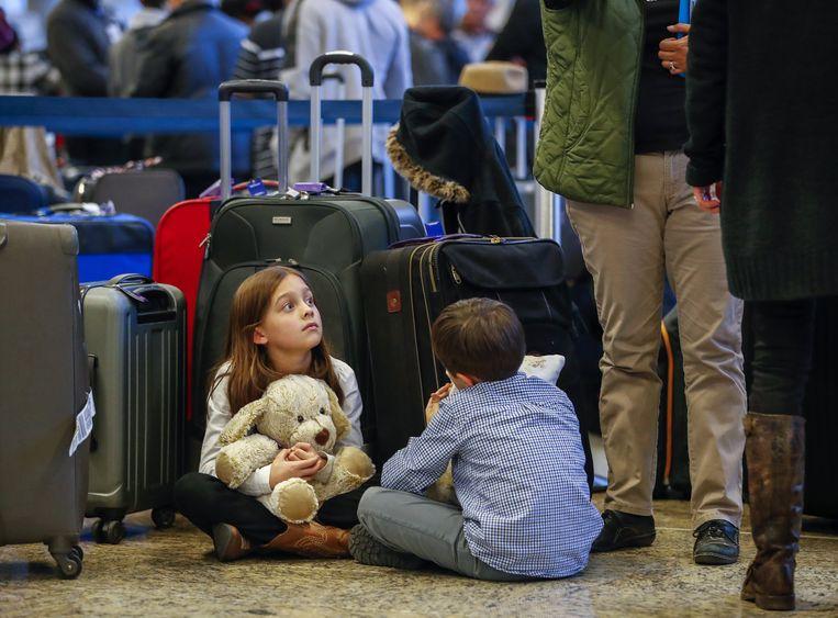 Kinderen wachten tot de stroomstoring voorbij is op de luchthaven van Atlanta.