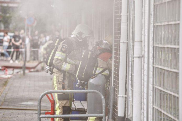 De brandweer bestrijdt het vuur in de snackbar.