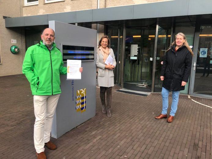 Rino Jonkers voor het gemeentehuis van Houten, met het referendum-verzoek in zijn hand. Rechts van hem zus Ellen Standhardt en sympathisante Jolanda Wijsmuller.