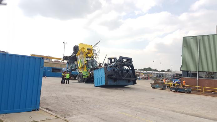 De grote gele heftruck is met lading en al omgevallen. De cabine waar de bestuurder in zat lijkt los te zijn geraakt van de machine.