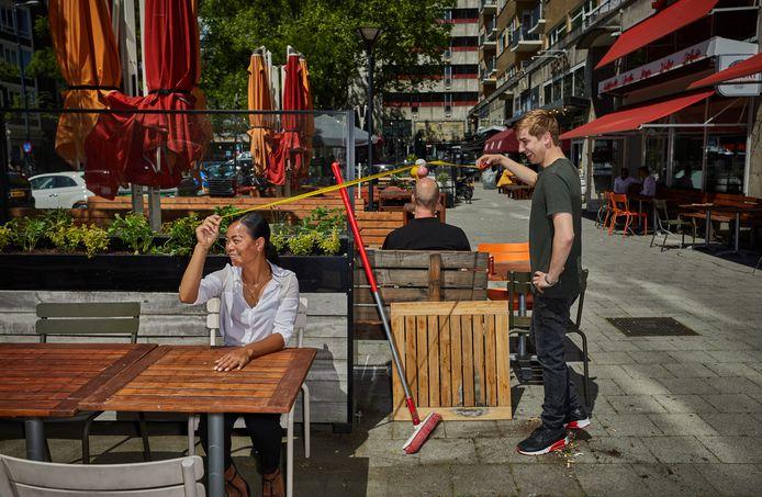 Medewerkers van restaurant Gusto aan de Schiedamse Vest meten de afstand tussen de tafels van hun grote terras.