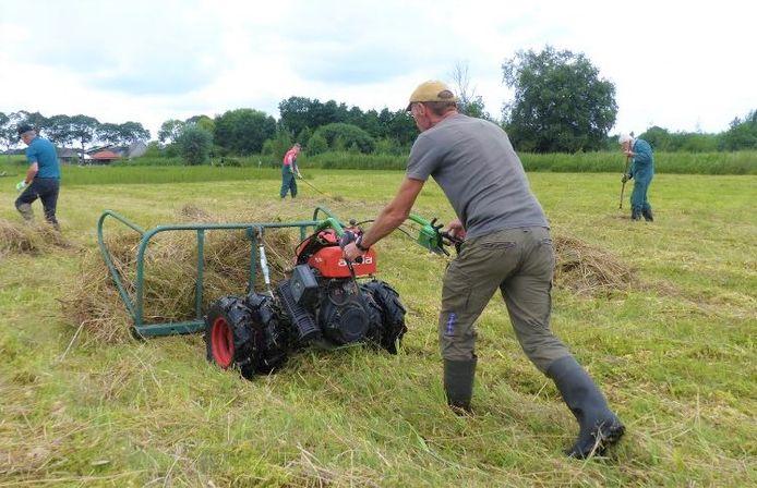 Vrijwilligers bezig met het wegwerken van de achterstand die is opgelopen met het maaien.