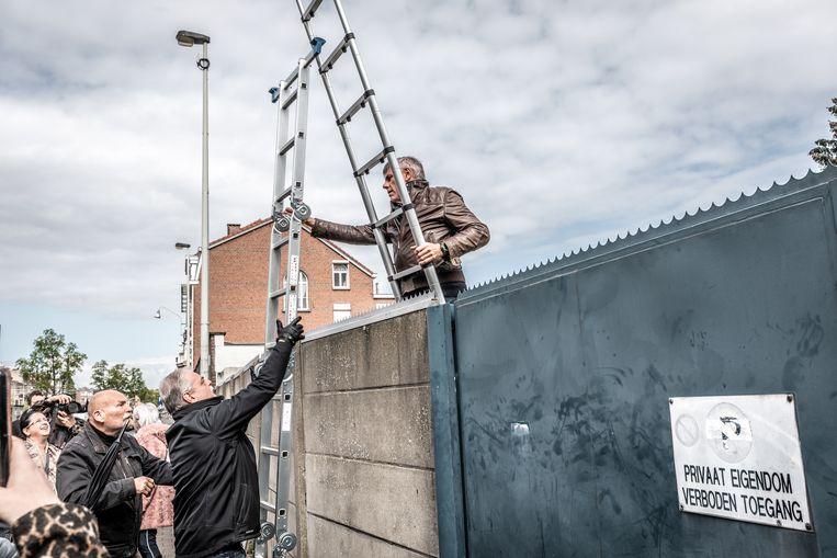 Met ladders klimmen Vlaams Belangers over de muur van het asielcentrum.