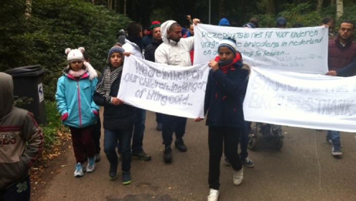 Vluchtelingen lopen met spandoeken als protest tegen de omstandigheden in de opvang in Nijmegen