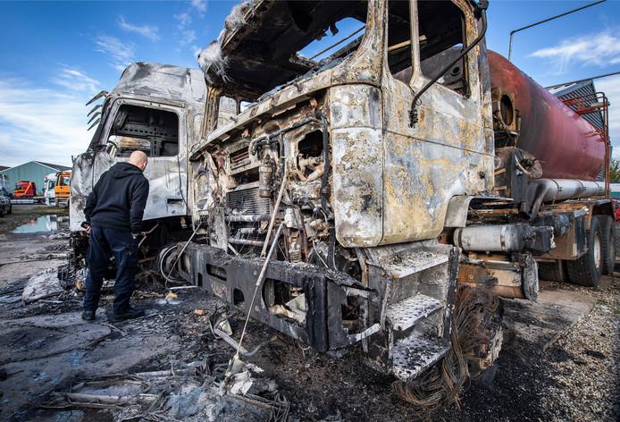 Een medewerker van de forensische opsporing aan het werk na een grote brand bij autobedrijf aan de Rouwenboschweg