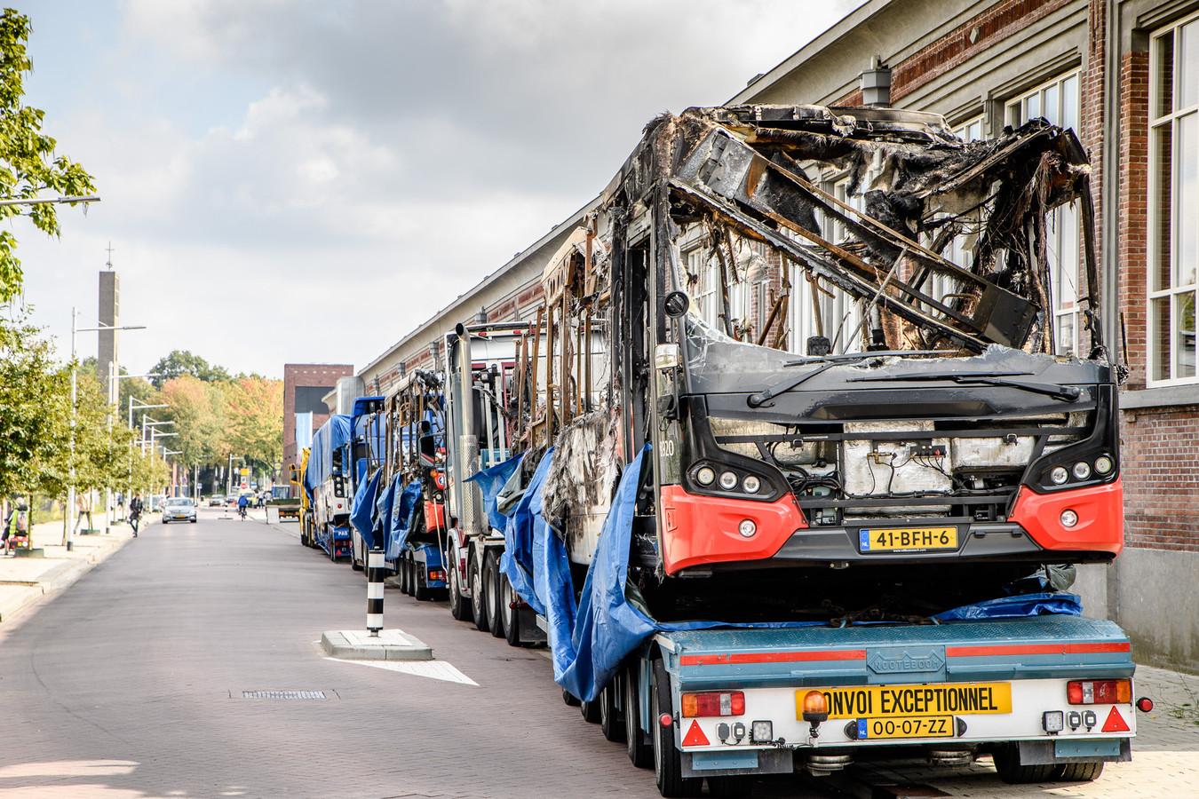 De door de brand verwoeste bussen uit de remise van Arriva worden afgevoerd.