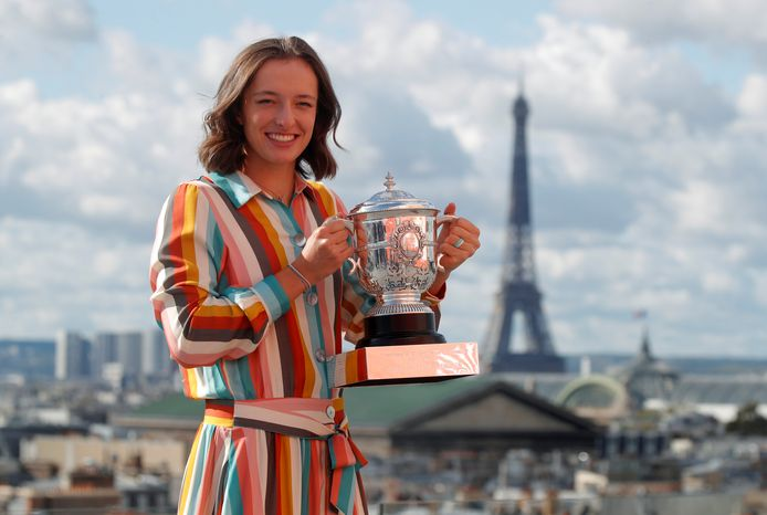 Iga Swiatek poseert met de trofee na het winnen van Roland Garros.
