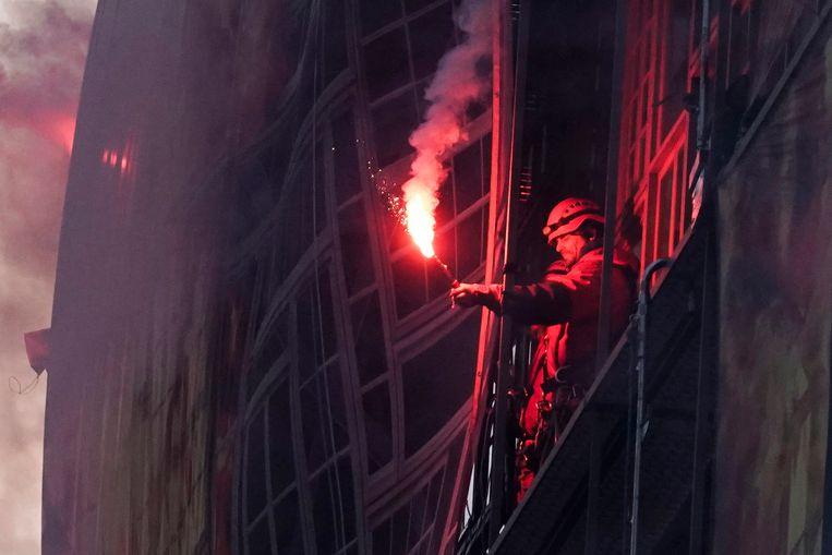 Actievoerder van Greenpeace met een fakkel bij het Europa-gebouw in Brussel. Beeld AFP