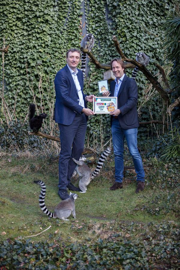 Alex van Hooff, Directeur van Burgers' Zoo (links) neemt de award van Edzard Gelderman van Queueup in ontvangst.